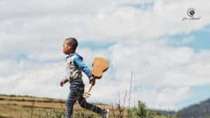 image of boy running and carrying a ukelele