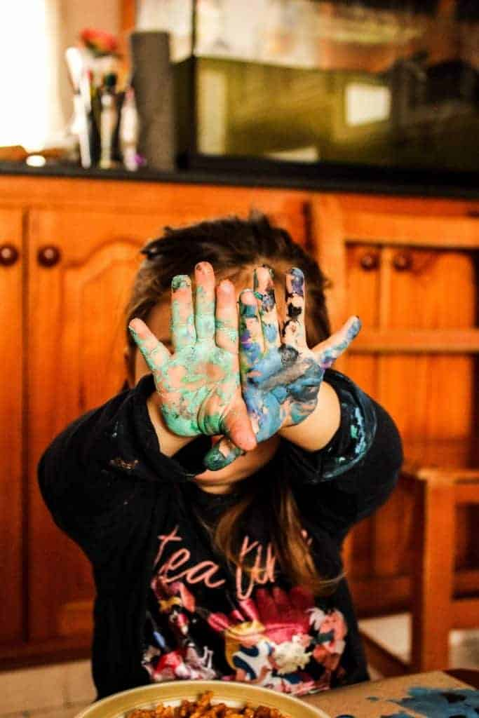 Image of girl with paint covered hands holding them in front of her face in homeschool mom tips