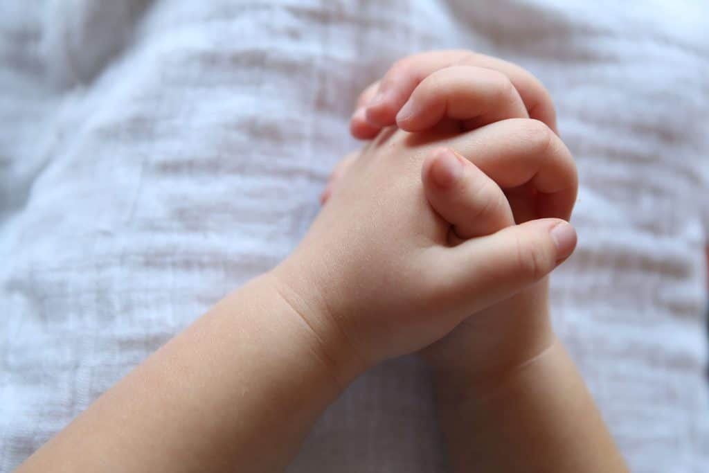 picture of a toddler's chubby hands with the fingers linked together for prayer