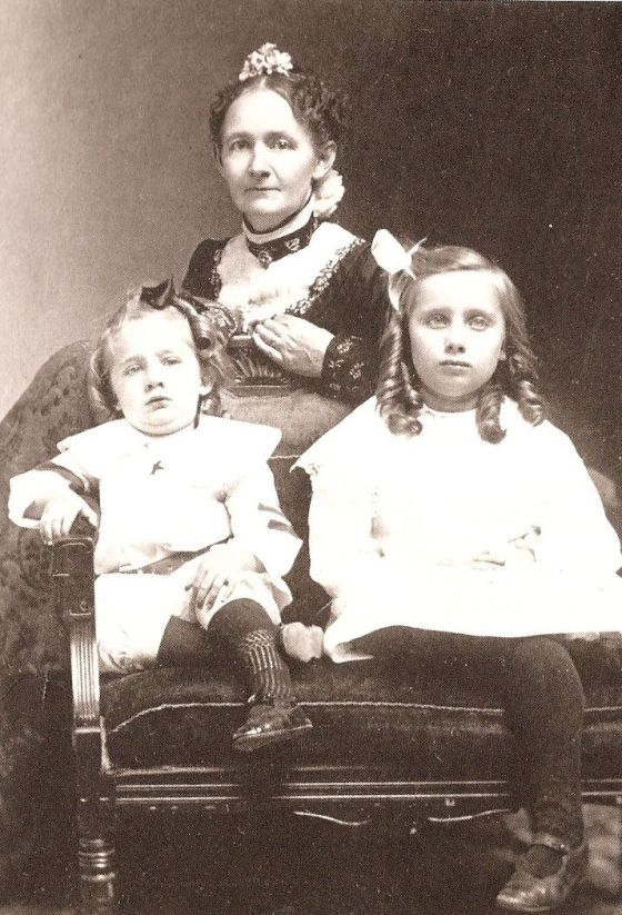 Black and white photograph of a woman in her 30s, Grandma Moses, in the middle with a toddler girl and young girl sitting in front of her.