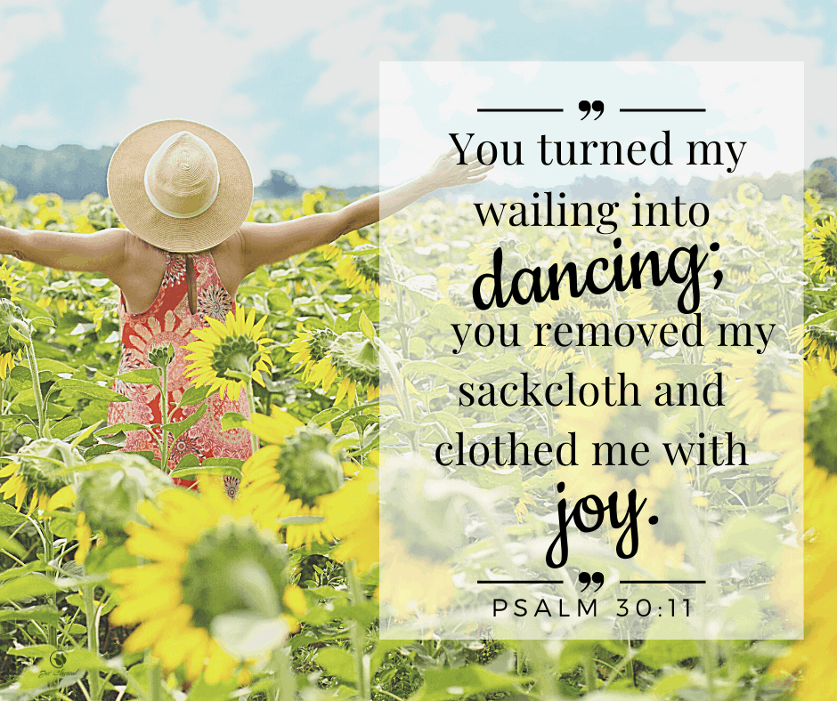"""Picture of back of woman in a red flowered dress and straw hat with a rim raising her arms up in joy as she stands in a field of sunflowers with the words from Psalm 30 verse 11, """"You turned my wailing into dancing; you removed my sackcloth and clothed me with joy."""""""