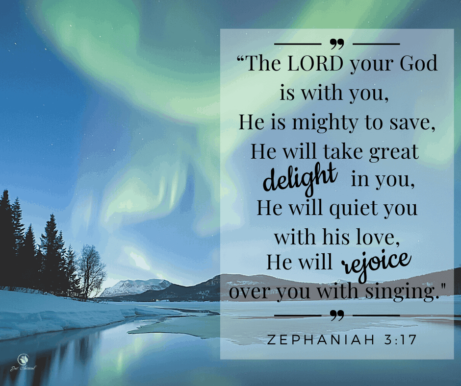 """Picture of winter scene in blue tones with silhouettes of trees on a snowy bank on the left, a lake towards the bottom of the picture and blue sky with green swirls of the aurora borealis filling the top 3/4 of the picture. Also the words from Zephaniah 3 verse 17 are written on the right side of the picture: """"The LORD your God is with you, He is mighty to save, He will take great delight in you, He will quiet you with his love, He will rejoice over you with singing."""""""