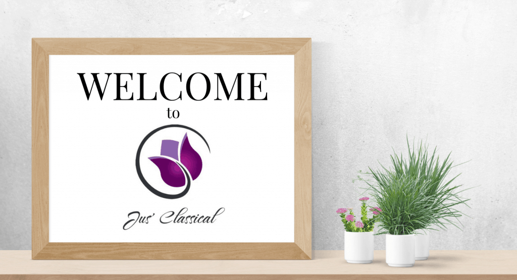 """Image of whiteboard with words, """"Welcome to Jus' Classical"""" next to 3 small plants in pots on a table."""