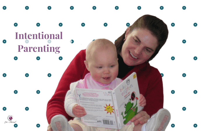 Image of woman with long brown hair holding a baby with blond fuzz for hair on her lap and reading a book. In the background are turquoise polka dots and the words Intentional Parenting.